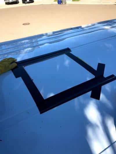 Cutting a hole for a fan alongside solar panels for a van roof